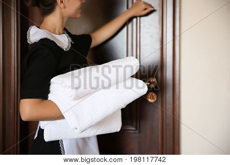 Chambermaid with clean towels knocking on door to hotel room