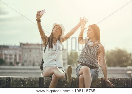 Two happy women are having fun together in the city. They are taking selfie. Image is intentionally toned.