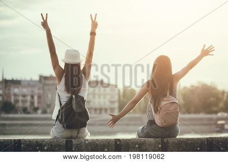 Two happy women are having fun together in the city in summer. Image is intentionally toned.