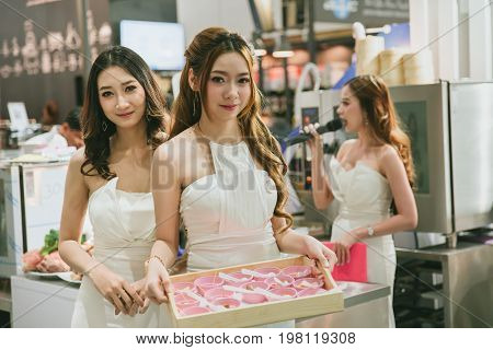 Bangkok. THAILAND - July 16 2017: Asian women pritty give food sample to customer in Food market industry expo at Bangkok.