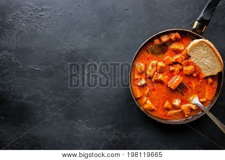 Stew With Bread In A Frying Pan On A Black Background