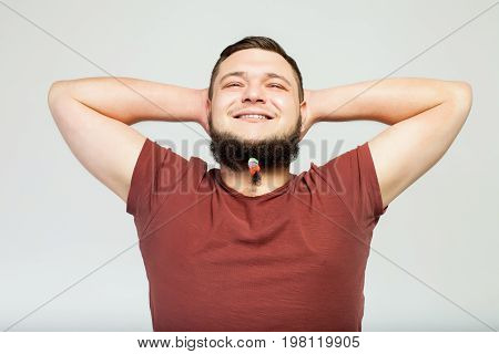 happy fat man portrait in profile with hair clips on long beard over gray background. Concept of comic, hairdo, hair style