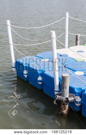 Plastic pontoon with the white pole for water activity in the large lake of the natural resort.