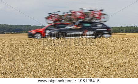 Vendeuvre-sur-Barse France - 6 July 2017: Blurred image of technical cars at high speed passing through a region of wheat fields in the Publicity Caravan before the cyclists during the stage 6 of Tour de France 2017.