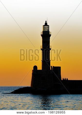 Lighthouse on sunset. Chania Crete Greece. Lighthouse silhouette at sunset. Golden sunrise sunset in sea red beacon lighthouse in Chania Crete Greece. A silhouette of a lighthouse at dusk.