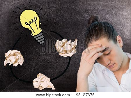 Digital composite of Man  next to light bulb with crumpled paper balls in front of blackboard