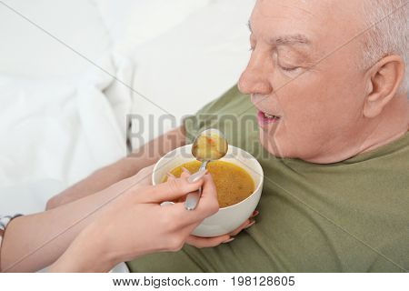 Young female volunteer feeding elderly man in light room