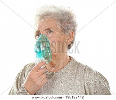 Elderly woman using asthma machine on white background