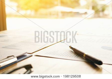 Pen on summary report on desk at office