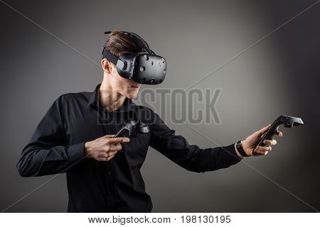 Attractive Man Wearing Virtual Reality Headset With Two Handheld Trackpads Or Controllers