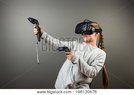 Child With Virtual Reality Headset And Joystick Playing Video Games