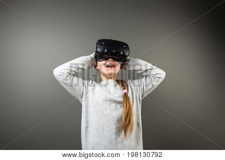 Girl Wearing Virtual Reality Goggles Standing On Grey Background. Vr Glasses. 360 Degrees. Virtual R