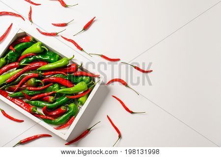 Hot red and green peppers, red chillies in the white wooden box on a white background