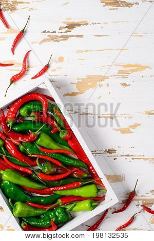 Hot red and green peppers, red chillies in the white wooden box on the old white wooden table