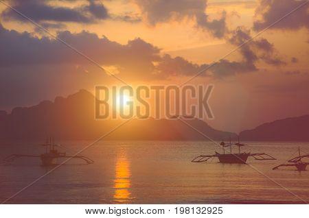 Sunset at El Nido. Banca boat anchored in a bay. Palawan island, Philippines.