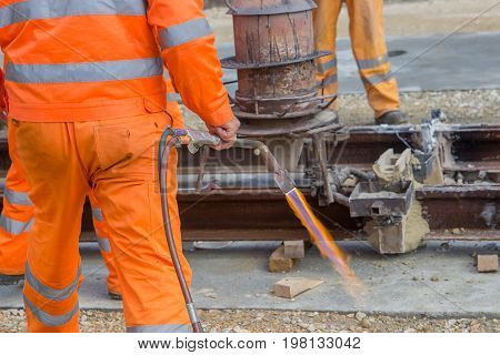 Workers In Orange Using An Oxy Fuel Gas Burner