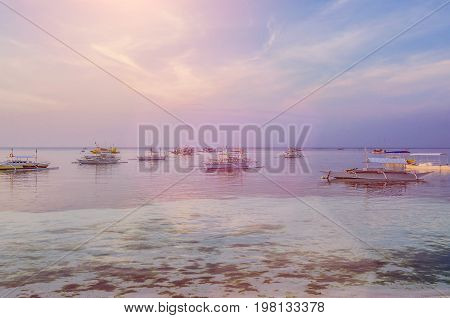 Banca boats anchored in the lagoon at Panglao Island in evening light. Bohol, Philippines.