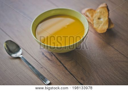 Pumpkin and carrot soup with cream and parsley