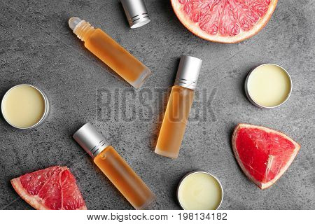 Bottles of perfume, jars and grapefruit on table