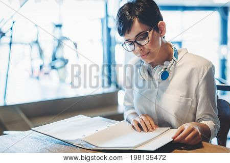 Portrait of clever student reading book in college library and studying