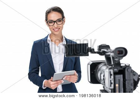 Attractive Female Newscaster With Digital Tablet Standing In Front Of Camera, Isolated On White