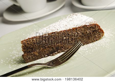 Piece of sweet cake with fork on the plate