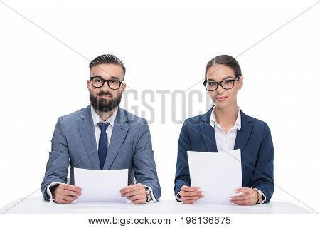 Two Newscasters With Papers Sitting At Table And Looking At Camera, Isolated On White