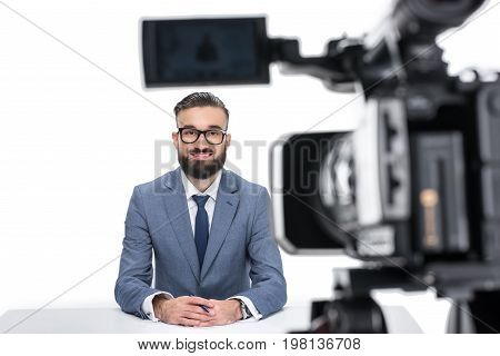 Smiling Male Newscaster In Suit Sitting In Front Of Camera, Isolated On White