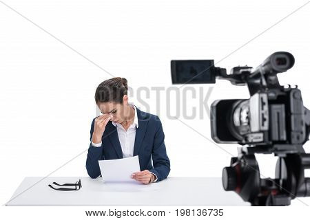 Tired Female Newscaster With Papers Sitting In Front Of Camera, Isolated On White