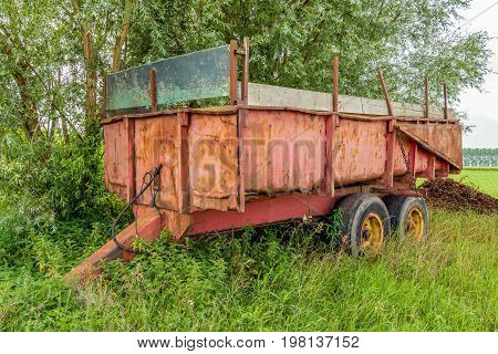 Neglected old and rusty farm trailer parked in the grass next to a field in the Netherlands.