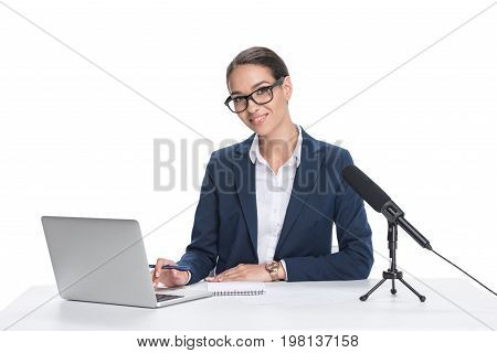 Attractive Smiling Female Newscaster Sitting At Table With Laptop, Notepad And Microphone, Isolated