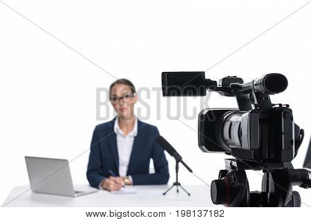 Female Newscaster Sitting At Table With Laptop And Microphone And Looking At Camera, Isolated On Whi