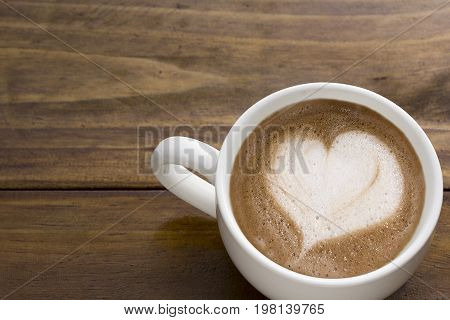 Coffee cup of LATTE ART Love symbol lover sign on wood table in coffee shop with copy space for text or graphic design. Cafe' latte cream in heart shape on top coffee mug on work desk - top view