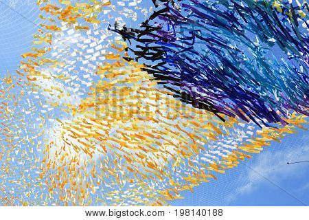 Abstract colorful background made from lot of diversity cloth against blue sky