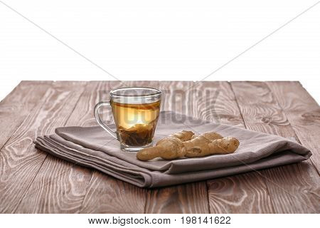 A close-up of a glass tea cup full of green tea isolated on a white background. A little cup of hot and healthy beverage next to ginger on a fabric and a wooden table. Organic beverage. Copy space.