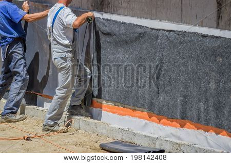 Workers Installing Wall Insulation 2
