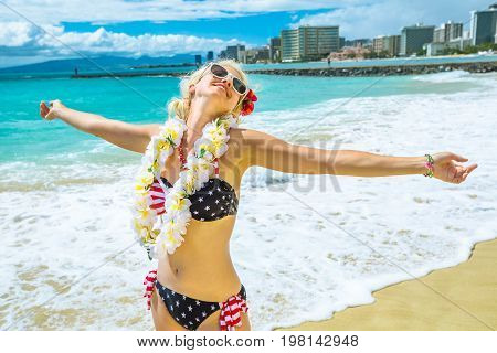 Happy female showing her her hawaiian lei necklace. Freedom woman with american flag bikini and white garland orchids in Hawaii. Waikiki Beach in Honolulu, Oahu. Tropical destination holiday travel.