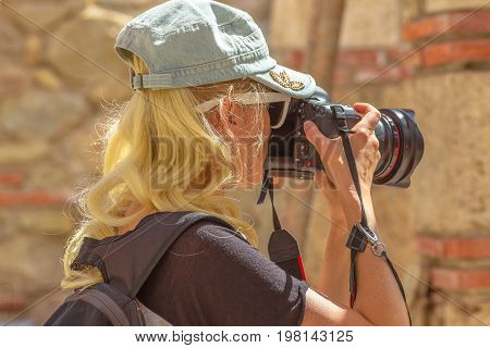Traveler woman photographer with camera takes picture. Portrait of caucasian blonde female shooting outdoor. Professional photographer takes photo during a trip. Travel and tourism concept.