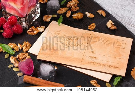 Beautiful composition of romantic postcards, fruity ice hearts, walnuts and leaves on a black plate on a gray wooden background. Pink raspberries, sweet cinnamon and a fresh drink next to a love note.