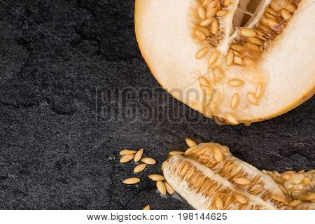 A close-up of ripe melon on a saturated black background. The raw melon cut in a half full of nutritious vitamins. Some seeds near the melon. Refreshing ingredients for vegetarian breakfast.