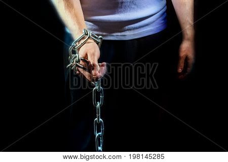 Man with chain on his hand on a black background