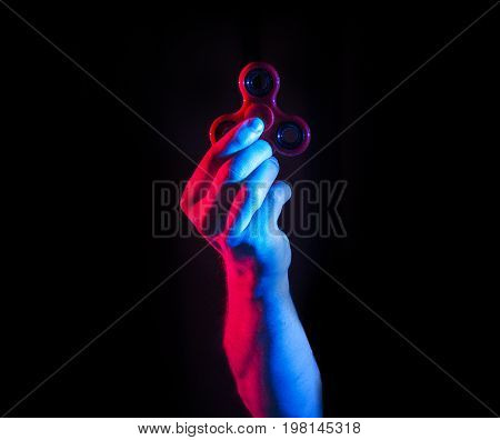 Man hold fidget spinner on a black background Minimalism style