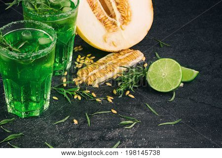 A close-up of half of a raw and ripe melon and cut juicy lime on a black background. Refreshing, natural green cocktails with tarragon leaves and citrus fruits. Summer exotic fruits full of seeds.