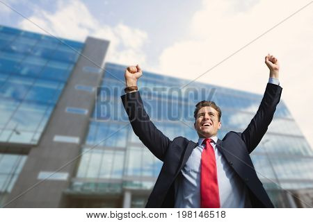 Digital composite of Excited business man standing against building background