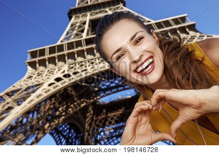 Smiling Woman Showing Heart Shaped Hands In Paris, France