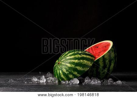 A round half of a summer refreshing watermelon on a black background. Watermelon is cut showing a hard, green rind, sweet watery reddish flesh and black tiny seeds. The big berry is full of vitamins.