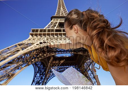 Woman Holding Map And Pointing On Eiffel Tower, Paris