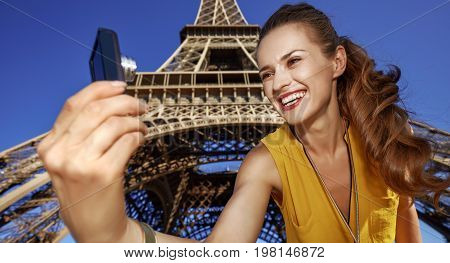 Woman Taking Selfie With Digital Camera Against Eiffel Tower