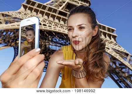 Woman Taking Selfie And Blowing Air Kiss Near Eiffel Tower