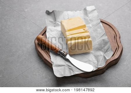 Cutting board with piece of unwrapped sliced butter and knife on grey background